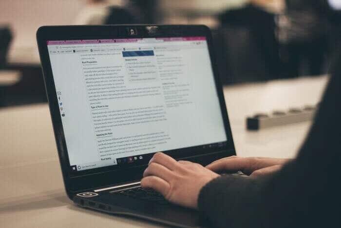 Foto de una persona escribiendo en una computadora portátil