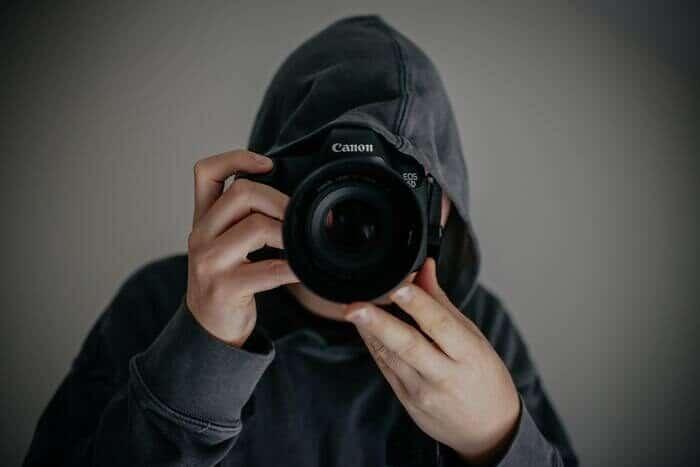 Foto de un chico con una sudadera con capucha y una cámara.