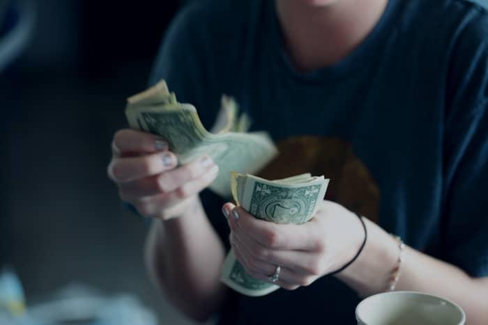 Un primer plano de una persona contando dinero.